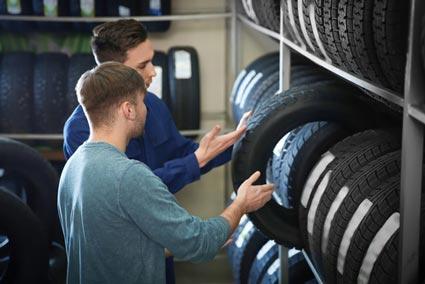 Mechaniker zeigt einem Kunden Reifen