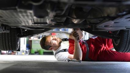 Automechaniker repariert unten am Auto